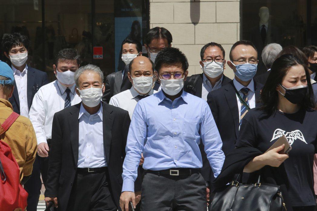 東京街頭,行人戴著口罩防疫。  美聯社
