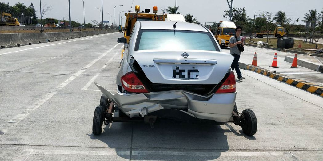 國產轎車車尾凹陷受損。記者謝進盛/翻攝