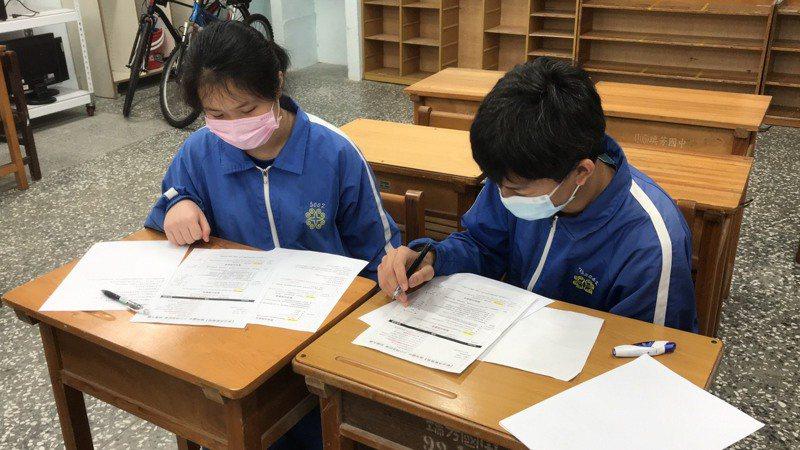 瑞芳國中學生蔡和曄(由右至左)、張緁恩討論校園特派記者相關內容。圖/新北市教育局提供