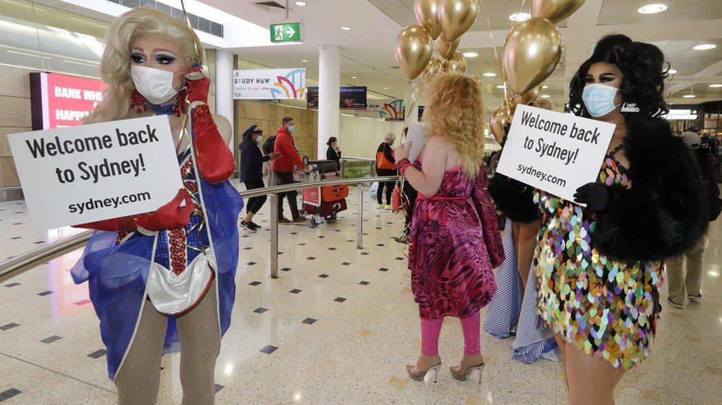 澳洲疫情趨穩後,本周啟動與紐西蘭之間的旅遊泡泡,幾位變裝皇后在雪梨機場歡迎旅客到...
