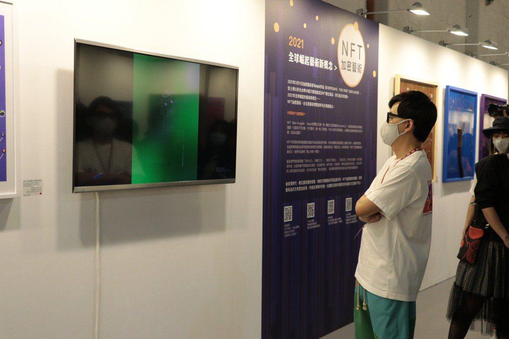 台北新藝術博覽會的松菸預展以NFT加密藝術區賣得最紅火。圖為藝人黃子佼從螢幕觀賞...