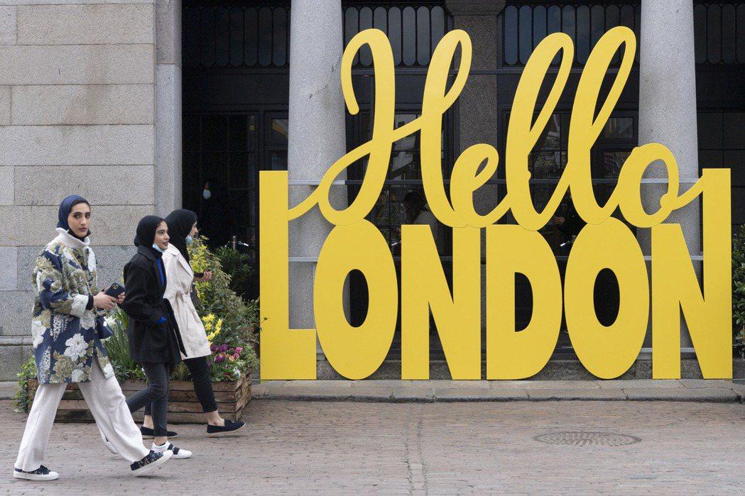 英國自12日起有條件解封,商店與理髮院等店家重新營業,圖為當天外出的逛街民眾。新...