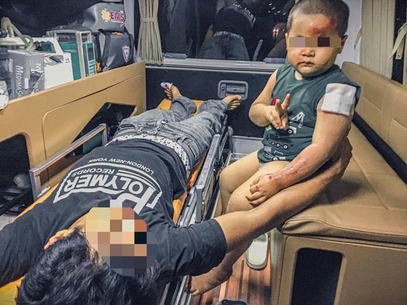 從照片可見,父親躺在救護車的擔架床上,3歲兒子在一旁,頭部和手臂擦傷流血,但向着鏡頭舉V,而爸爸的左手則輕輕搭着兒子的背部。(fb「Rattamanee Saynui」圖片)