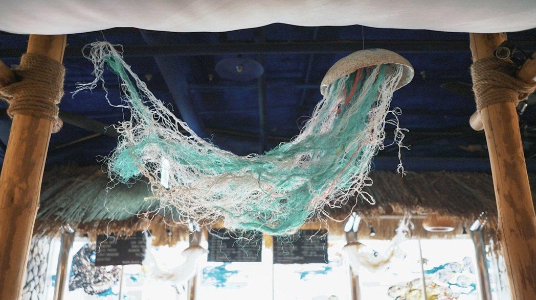 經過清洗後的漁網塑膠袋為原料再製的「塑膠水母」,除了呼應店內窗景畫,也帶來海洋的...