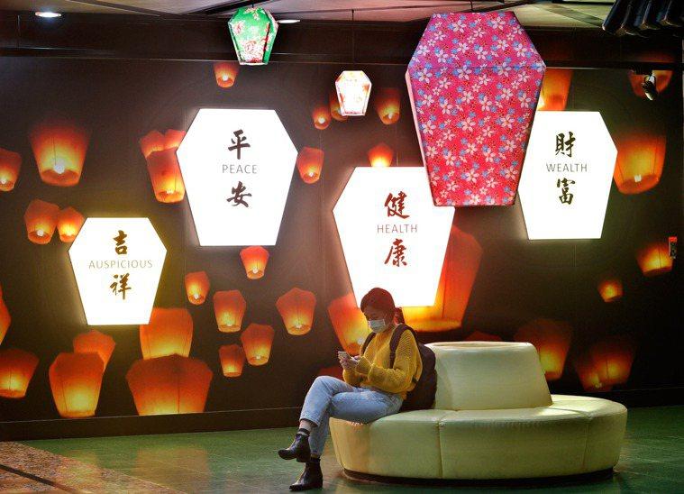 圖為桃園機場天燈主題候機室內,一名旅客戴著口罩等候飛機起飛,背景是段健康平安許願...