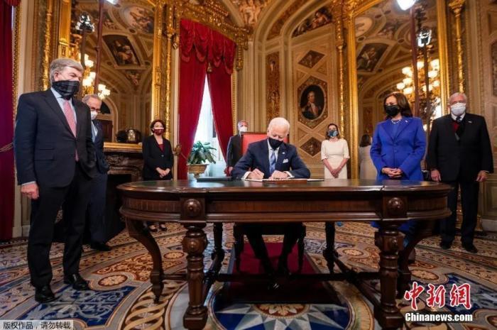 圖美國總統拜登就職後簽署一系列文件。中新網