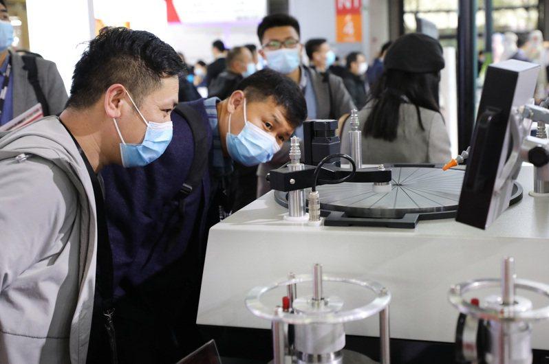大陸當前全力採購晶片。圖為今年三月中旬上海舉行中國國際半導體展,參觀者近距離觀看一台正在演示的晶圓研磨拋光設備展品。(新華社)
