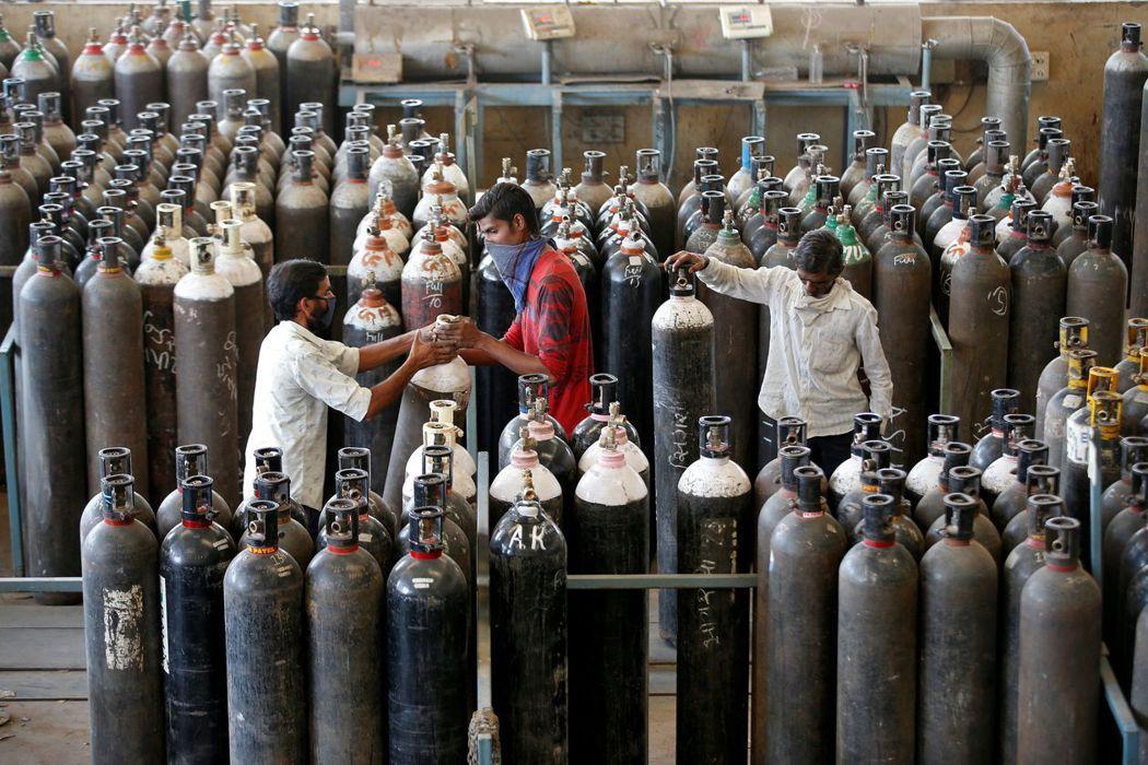 圖為當地人民在艾哈邁達巴德一家工廠補充氧氣。 圖/路透社