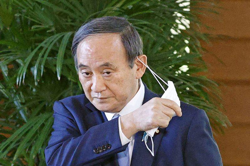 日本首相菅義偉廿六日在官邸脫下口罩準備接受記者訪問。(美聯社)