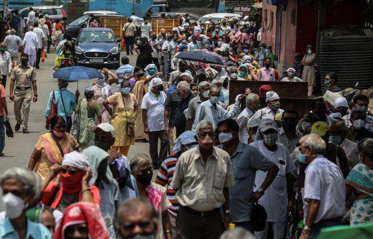 新冠疫情持續狂燒,印度孟買民眾大排長龍等待接種疫苗。歐新社