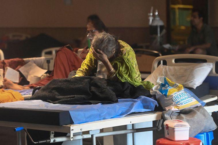印度新冠病毒患者廿七日在新德里一座宴會廳改裝的臨時醫院休息。印度疫情失控,醫院病...