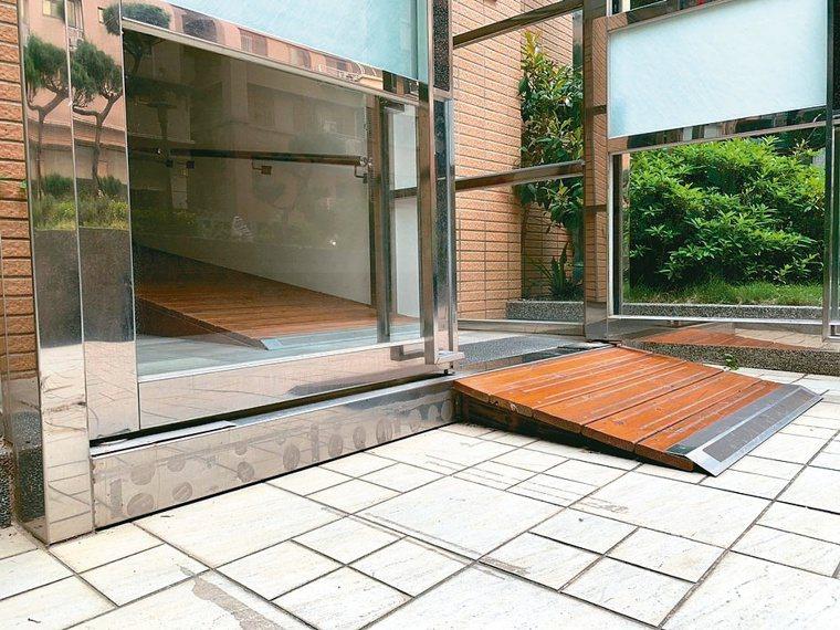 出電梯須面對三層階梯與梯間門外的一階高度差,現在鋪上木棧板改善。圖╱林萱宜提供