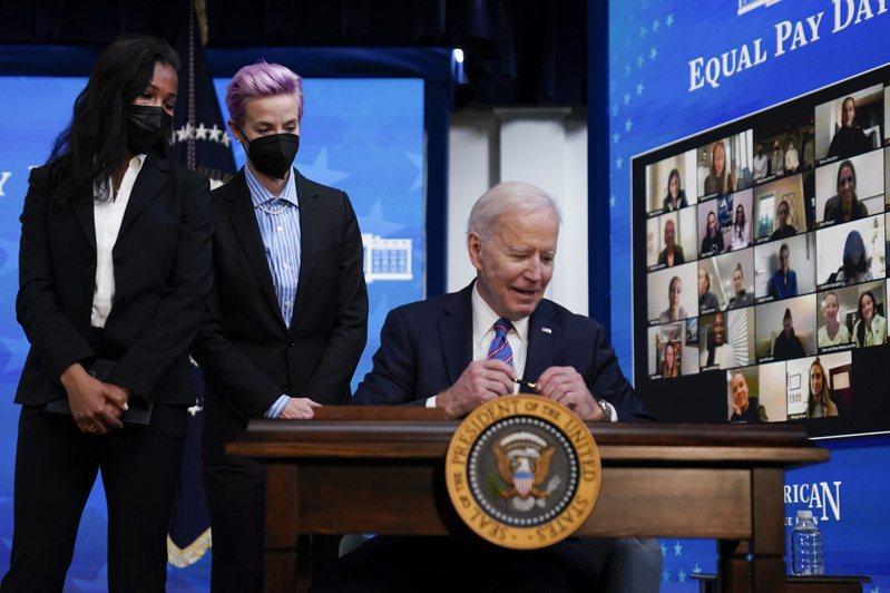 美國總統拜登(右)三月廿四日曾在白宮簽署命令,公告聯邦政府支持同酬日活動,推動兩性同工同酬。(美聯社)