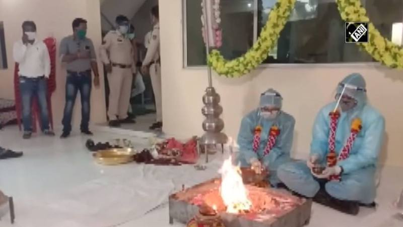 圖為印度亞洲新聞國際通訊社4月27日在YouTube發布的影片截圖,顯示印度中央邦一對新人身穿個人防護裝備舉行婚禮,有警員在場監督。(ANI News Official YouTube Channel)