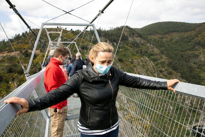 民眾在走阿羅卡516吊橋時,緊握橋的兩側。路透