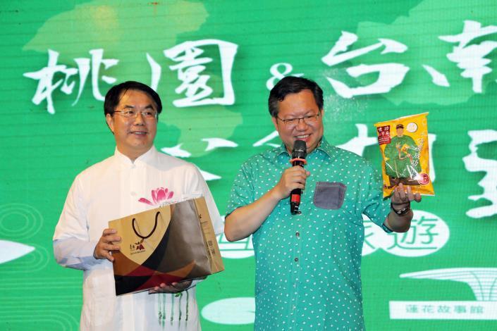 桃園市長鄭文燦(右)去年7月率隊到台南,與台南市長黃偉哲(左)合體共同行銷兩地觀光。圖/擷取自台南市政府網站
