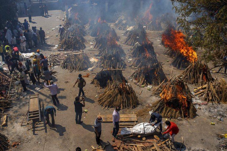 圖為印度新德里在一處廣場上,焚燒因新冠肺炎死亡的罹難者屍體。美聯社