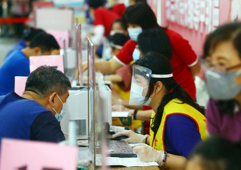 綜合所得稅申報今天登場,工作人員戴上防護裝備協助民眾報稅。圖/聯合報系資料照片