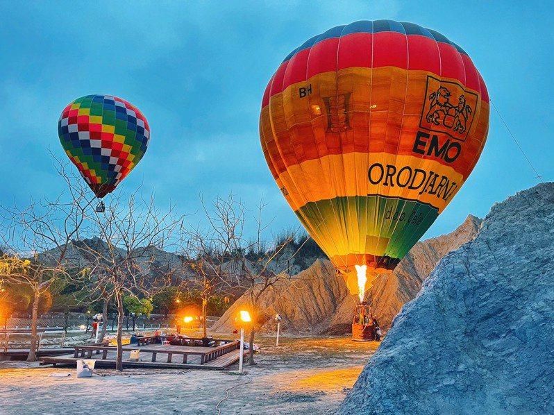 田寮月世界風景區測試熱氣球,色彩繽紛的巨大氣球與光禿背景形成強烈對比。圖/高市觀光局提供