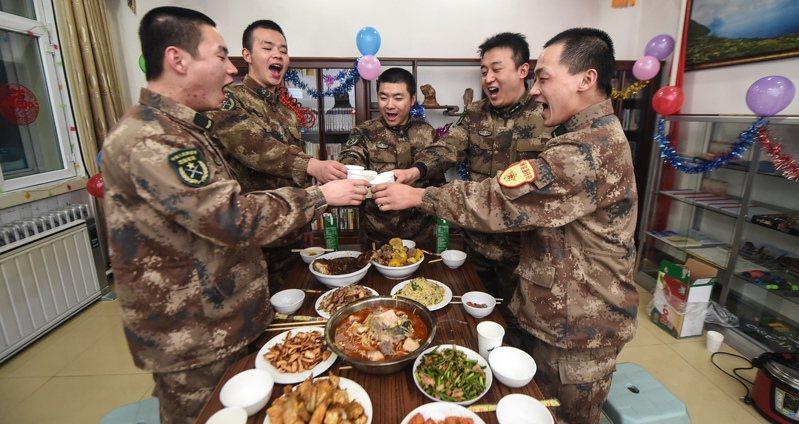 今年中國解放軍的春節菜單,8菜2飯1湯且全是「硬菜」,意思是平常少見的大餐,圖為2015年長白山天池哨所官兵在吃年夜飯前用果汁乾杯。新華社