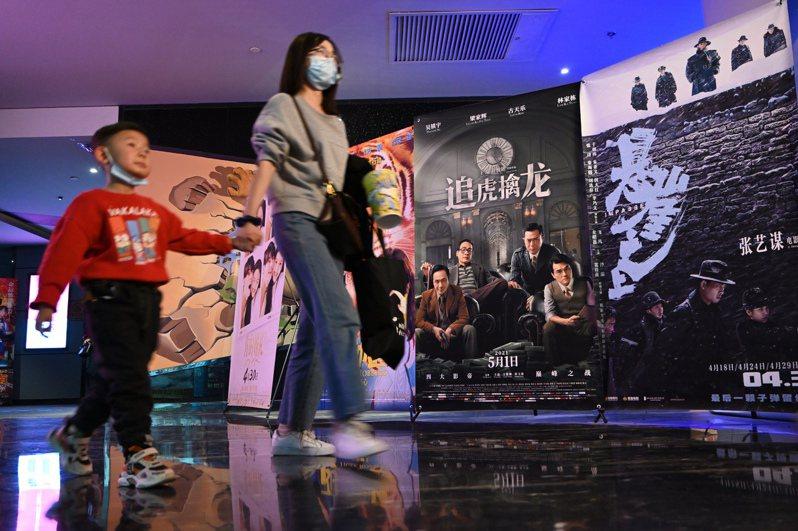 大陸2021年電影「五一檔」票房亮眼。圖為內蒙古呼和浩特市一家影院內,家長領著小朋友準備觀看電影。(中新社)