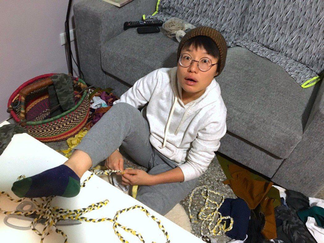 用二手衣布料與垃圾進行佈景編織,圖為編繩過程。 圖/鄒雅荃提供