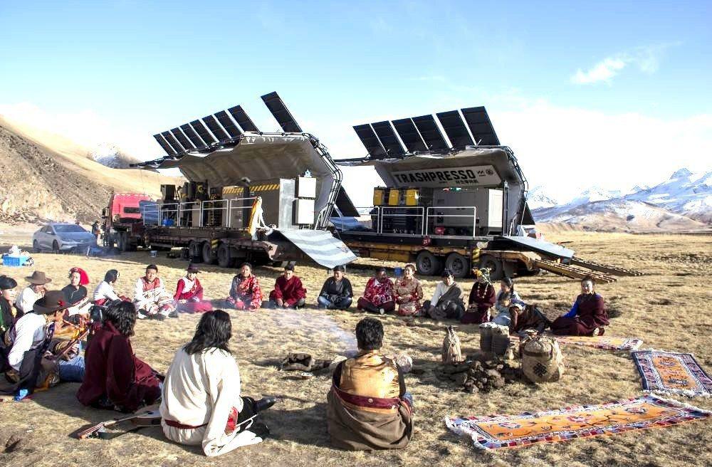 西藏人圍坐在位於青海的「環生零耗機Trashpresso」前。機器將消費後的廢物...