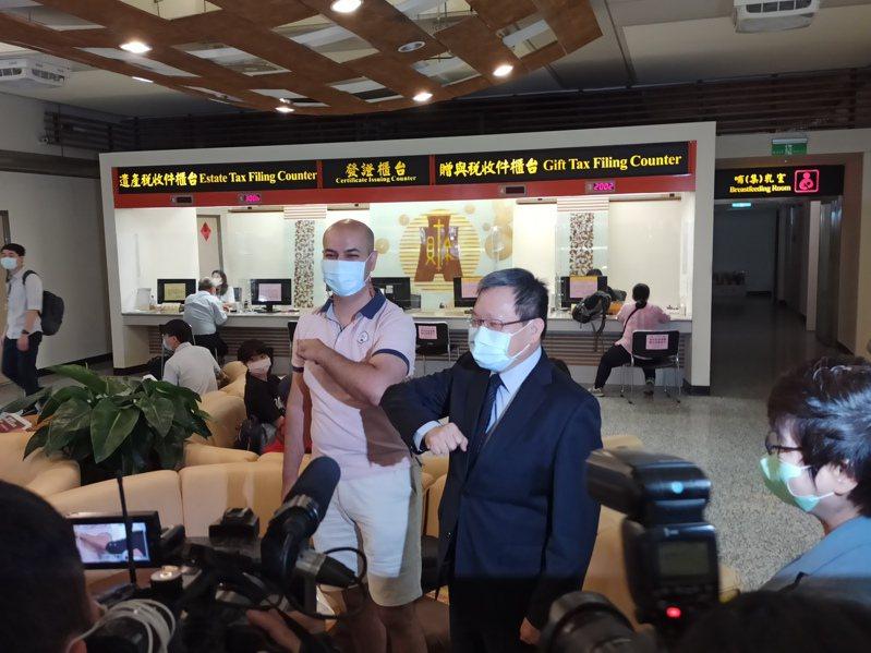 財政部長蘇建榮視察報稅情形,與現場外國人「互碰手肘」打招呼。攝影/記者翁至威