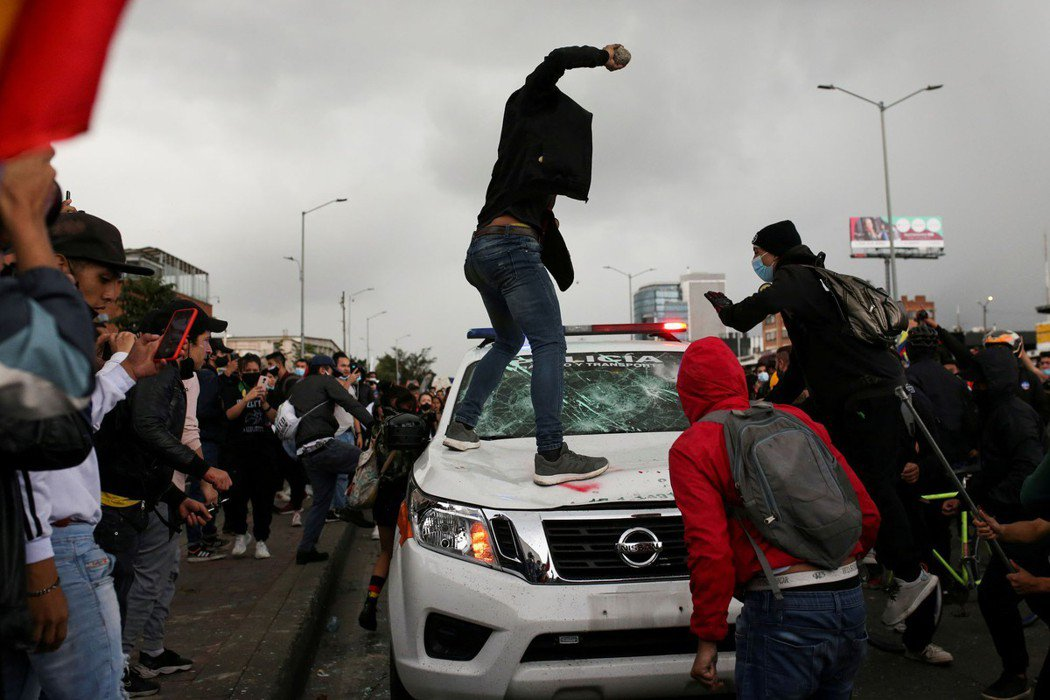 圖為用石頭擊碎警車玻璃的示威者。 圖/路透社