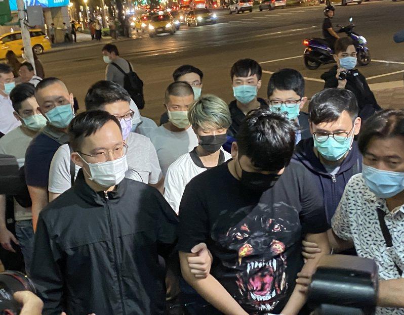 兩名黑衣人3日晚間在台北一間餐廳丟蟑螂後逃逸。警方掌握涉案犯嫌為4男1女,4日下午先查獲游姓女嫌,晚間再拘提許姓男子(前排右2)、曹姓男子(2排左2)等4名男性犯嫌到案。圖/中央社
