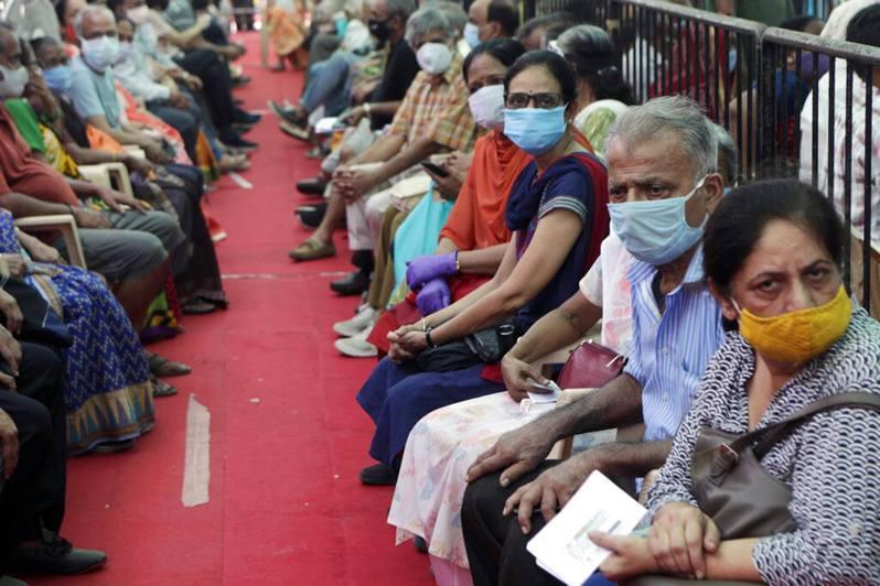 印度新冠肺炎疫情嚴峻。圖為孟買民眾排隊等候接種新冠肺炎疫苗。美聯社
