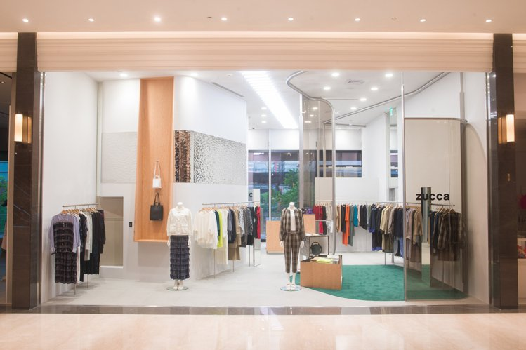 中性色調的綠色地毯、布簾,為冷調的微風南山ZUCCa女裝店面增添柔和、溫暖的氛圍...