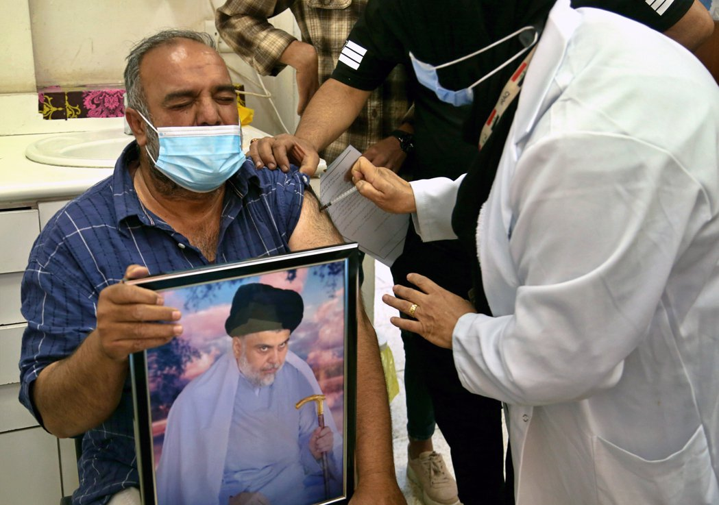 圖為伊拉克當地人在施打疫苗之時,握著什葉派穆斯林的領袖之一——穆克塔達·薩德爾的...