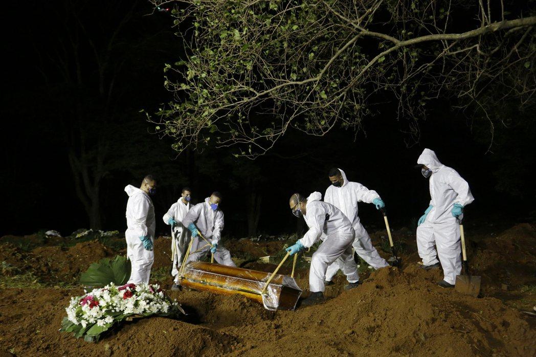 巴西疫情依然嚴峻,圖為工作人員正在埋葬因新冠肺炎逝世的患者。 圖/美聯社