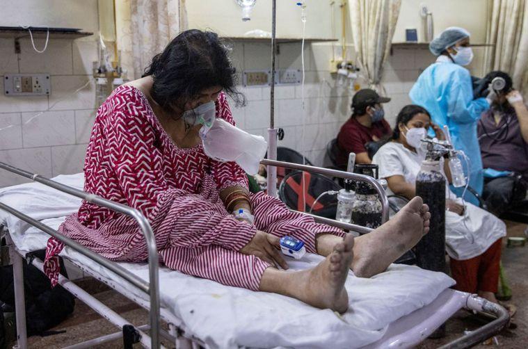 一名新冠病患一日戴著呼吸器,坐在新德里聖家醫院急診室病床上。(路透)