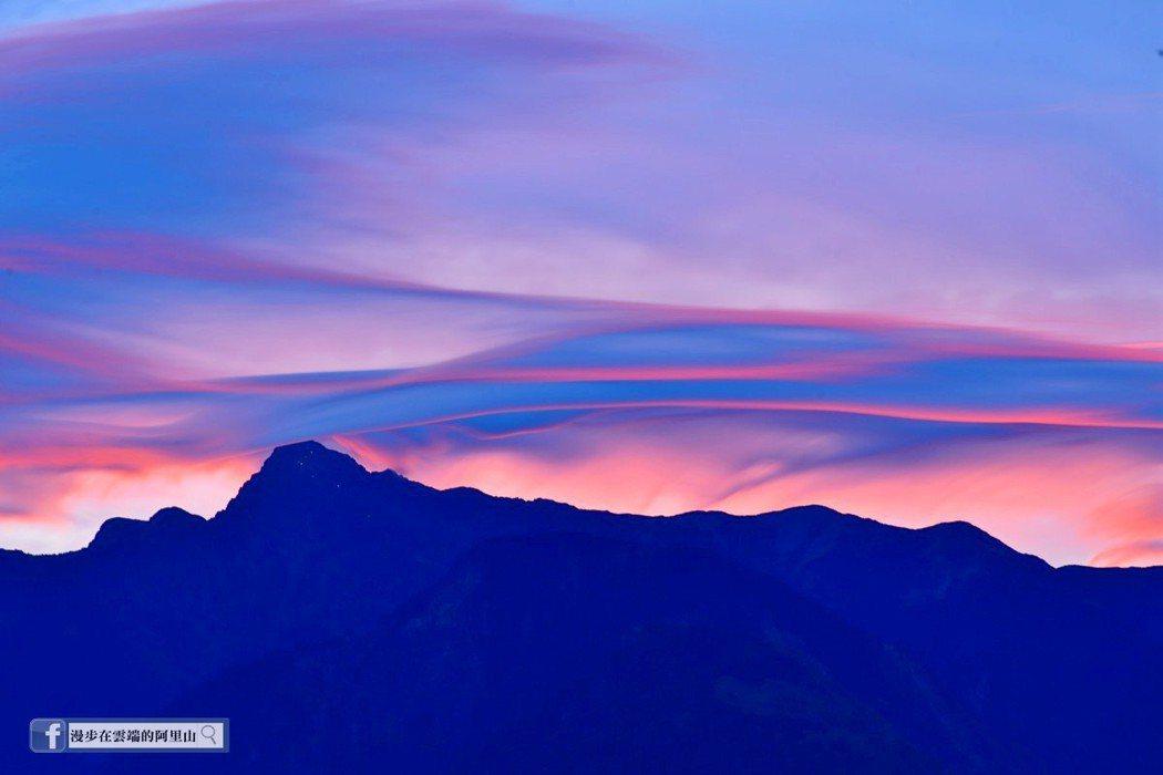黃源明說,小笠原山遠眺玉山群峰的莢狀火燒雲,主峰山頭下可見登頂山友的燈光照明。圖...