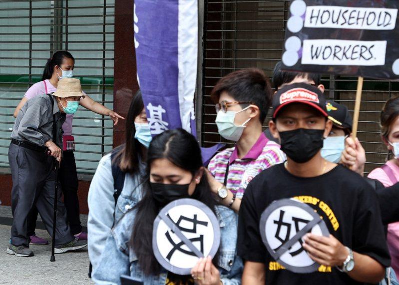 台灣移工聯盟與看護移工昨赴勞動部前抗議,要求勞動部提高家務移工勞動條件。一名被照顧的長者,恰巧在看護移工的攙扶下經過抗議現場。記者侯永全/攝影