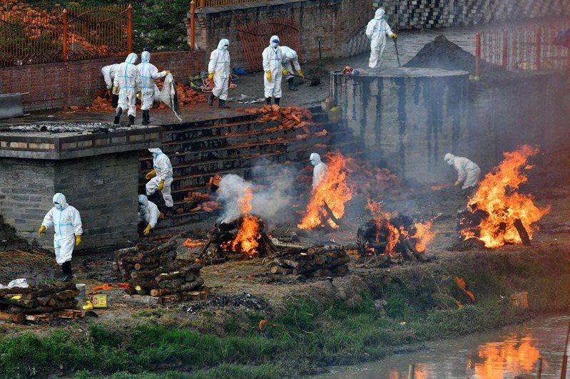 印度染疫死亡人數不斷攀升,圖為5月5日在加德滿都的火葬場上,身穿個人防護設備服的工人努力擴大火葬場。(法新社)