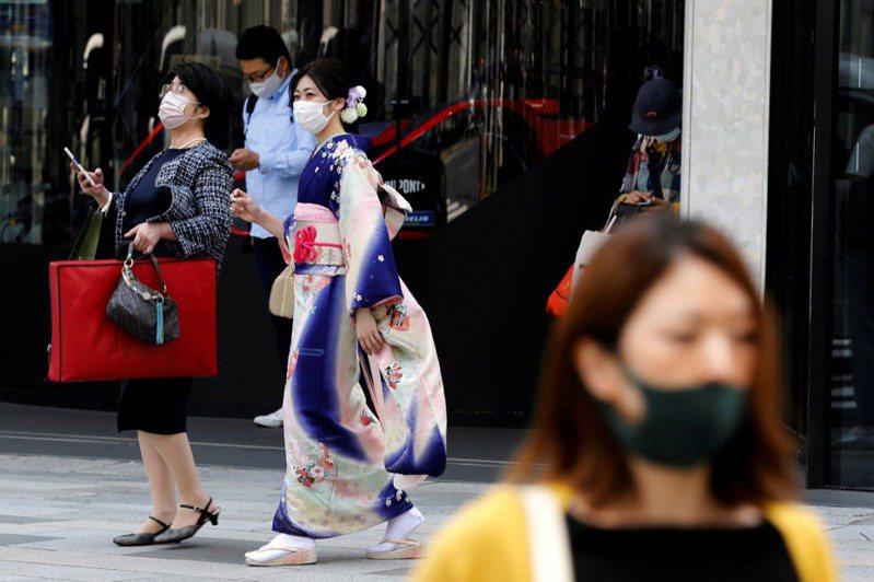 日本新冠肺炎疫情嚴峻,今年夏天將舉辦的「東京奧運」引起民眾質疑聲浪。圖為東京街頭穿著和服的婦女和戴著防護口罩的行人。 路透社