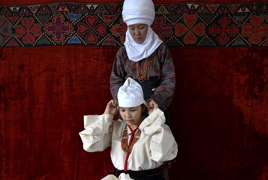 雖然搶婚「傳統」早在2013年就遭政府明訂禁止,但仍時常發生。圖為一名女性正在穿...