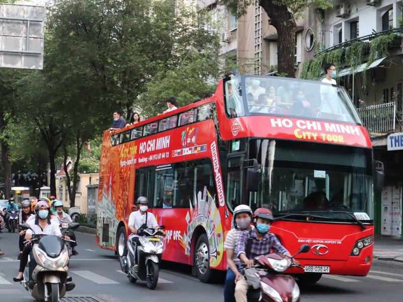 越南4月下旬再度爆發COVID-19本土疫情,超過1300萬人口的最大都市胡志明市自7日起禁止30人以上公共聚會。圖為搭載遊客穿梭胡志明市街頭的觀光巴士。中央社