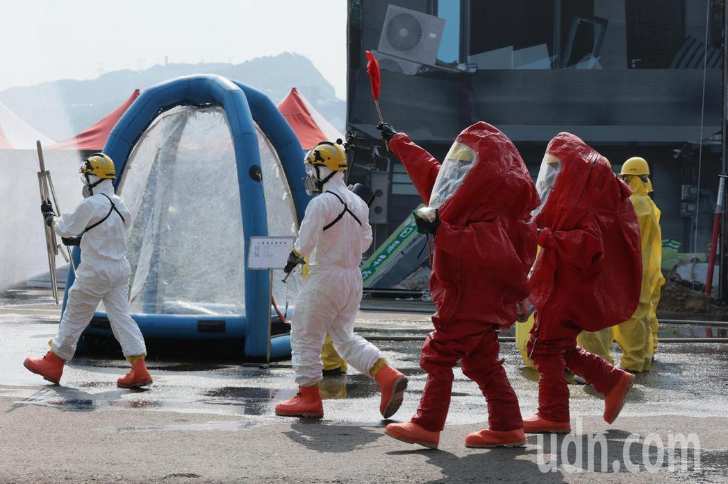 基隆市府在台船辦理災害防救演習,模擬化學槽車翻覆情境,穿著A級防護服的救災人員進...