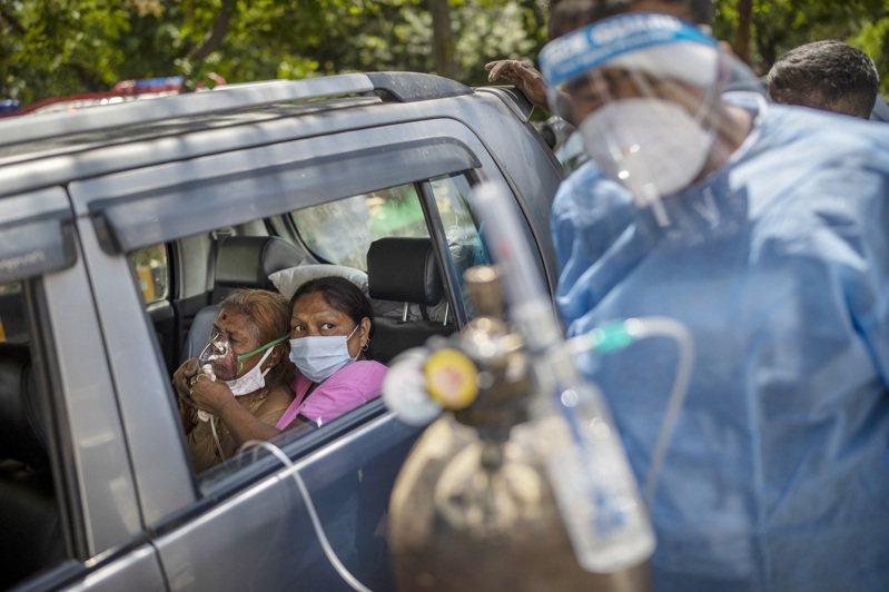印度疫情急速惡化,醫院甚至氧氣短缺,新德里一名患者在車內呼吸氧氣。 (美聯社)