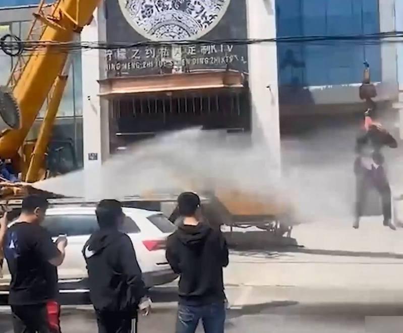 河南爆出低俗婚鬧,1名新郎被吊起用高壓水柱狂射,他無力反抗,只能掩面自保。圖/微博影片截圖