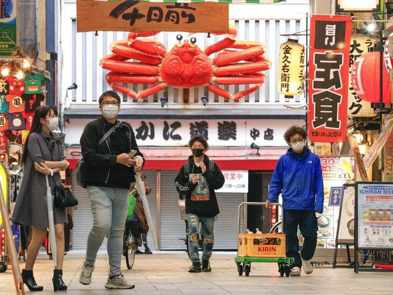 日本疫情持續升溫,7日新增148例死亡病例,再創歷史新高;其中50死集中大阪府,可看出大阪府在這波疫情是日本最嚴重的地區之一。圖為大阪民眾戴口罩上街情景。美聯社