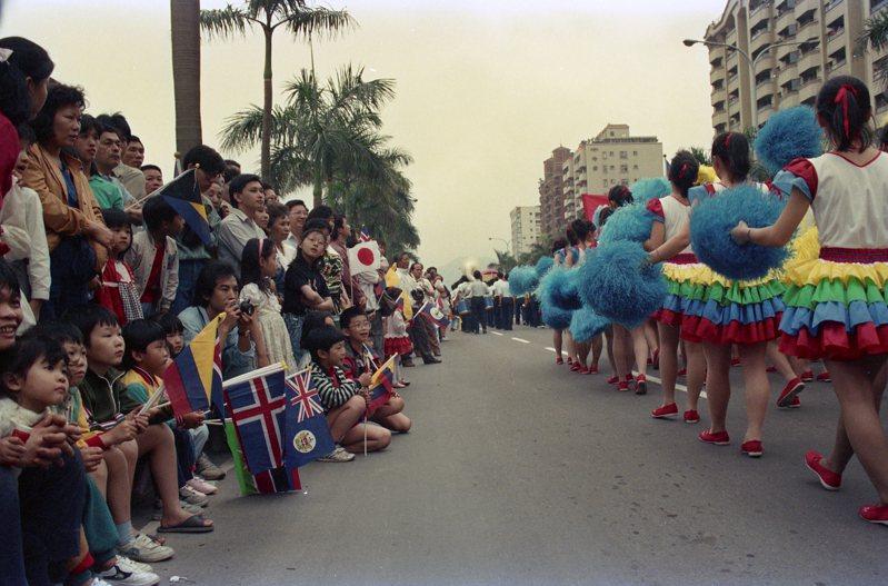 場邊群眾手持多國國旗參與花車遊行。圖/聯合報系資料照片
