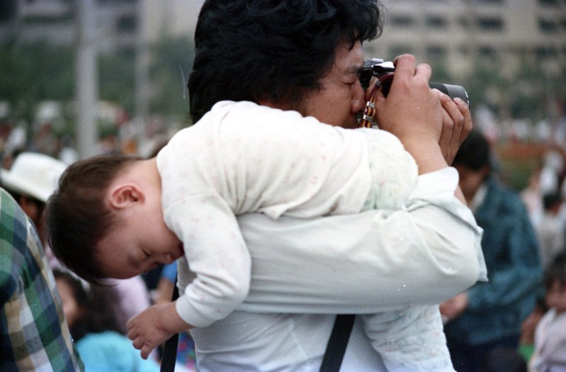 民眾拿起相機捕抓捉畫面,孩子則在肩上睡得香甜。圖/聯合報系資料照片
