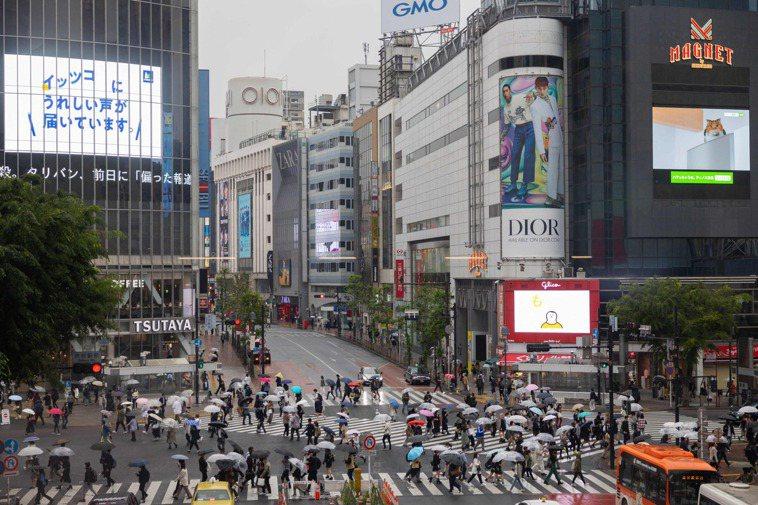 日本民眾七日經過東京涉谷區街頭。(法新社)