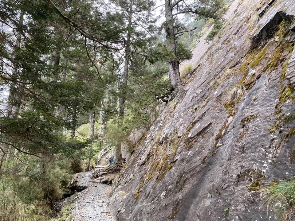 通過玉山大峭壁應觀察上方岩層是否出現新痕、異聲或鬆動裸岩,以免遭落石擊中。圖/玉...