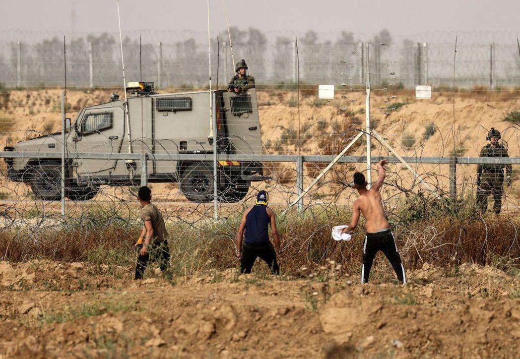 圖為5月9日在加薩邊界地帶,巴勒斯坦青年朝以色列警察投擲石頭。 圖/法新社